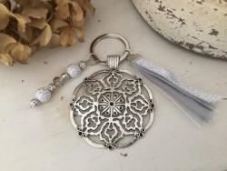Porte clés original au médaillon arabesques, perles et pompon