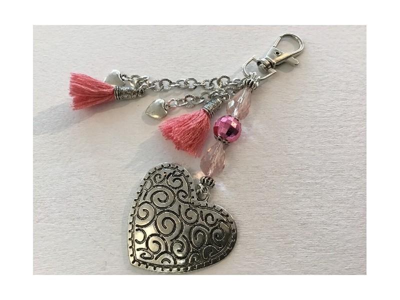 Bijou de sac au coeur en métal et pompons roses