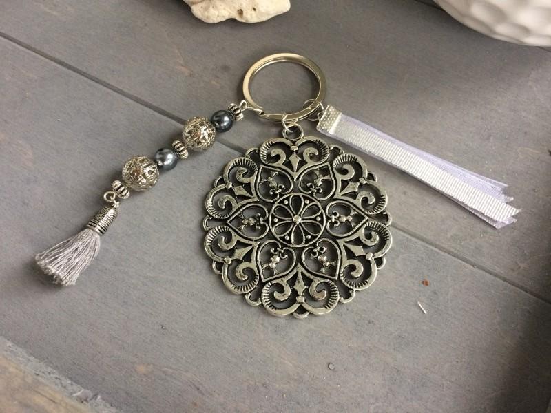 Porte clés médaillon argenté, rubans et breloque