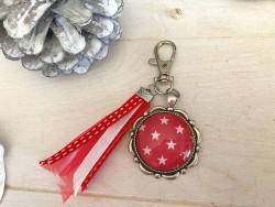 Bijou de sac aux étoiles blanches sur fond rouge et breloques